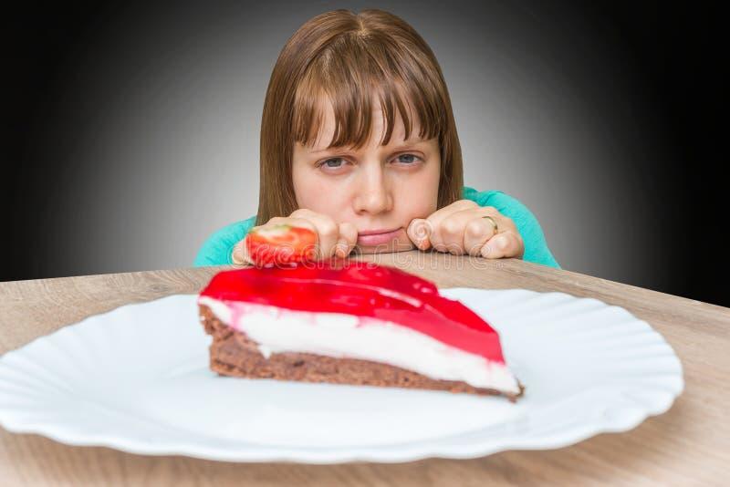 A mulher não pode resistir a tentação e não quer comer o bolo doce foto de stock