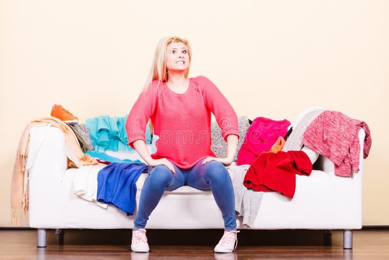A mulher n?o conhece o que vestir o assento no sof? imagens de stock royalty free