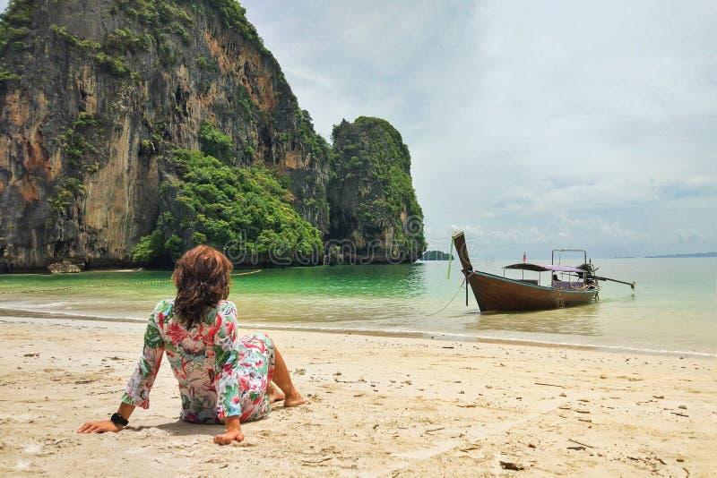 Mulher na areia que olha uma praia do paraíso imagem de stock