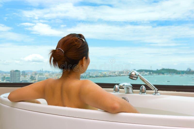 Mulher na banheira que olha a opinião do mar fotografia de stock royalty free