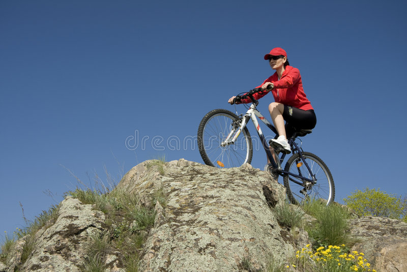 A mulher na bicicleta da montanha foto de stock