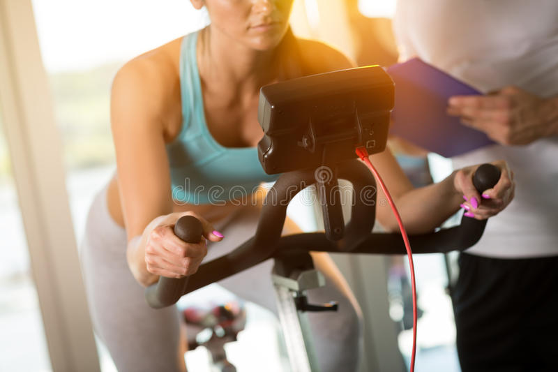 Mulher na bicicleta de exercício no gym fotografia de stock