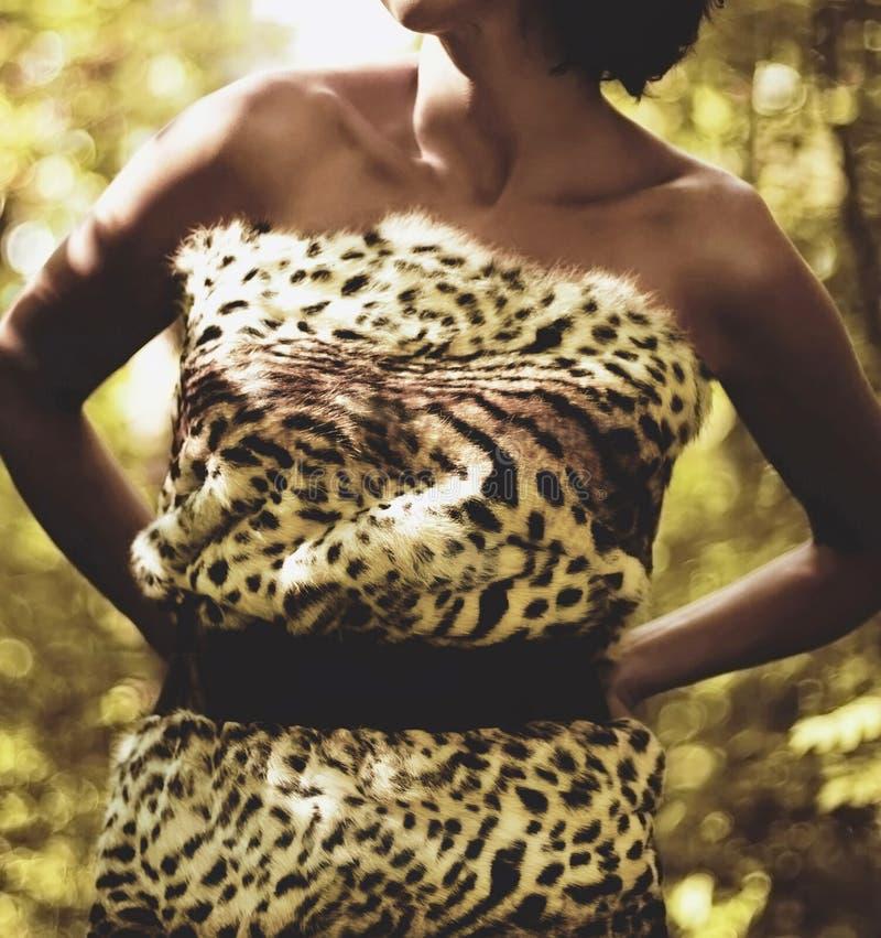 A mulher na cópia da pele do leopardo veste a floresta selvagem da selva foto de stock