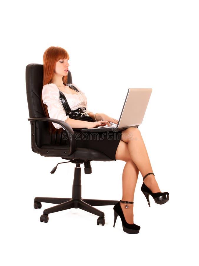 Mulher na cadeira com portátil fotos de stock royalty free