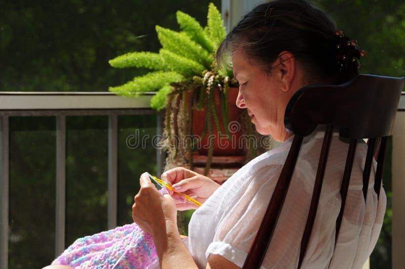 Mulher na cadeira de balanço usando o crochet foto de stock