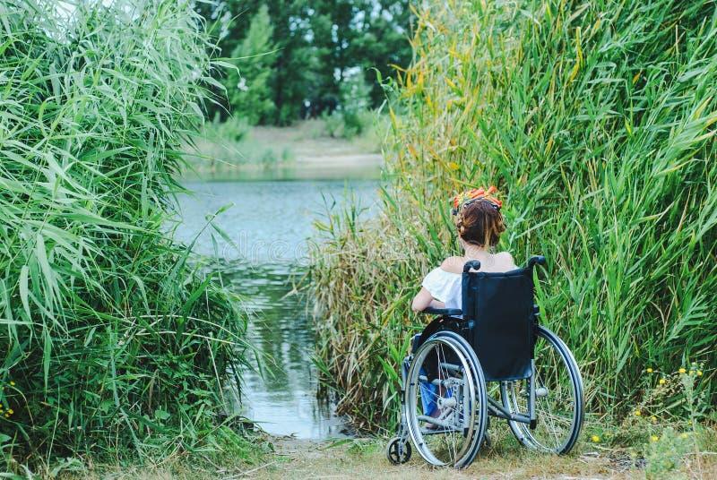 Mulher na cadeira de rodas, apreciando o tempo que olha o lago fotografia de stock royalty free