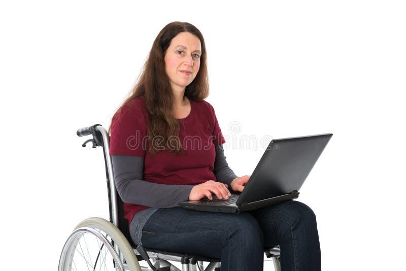 Mulher na cadeira de rodas com computador fotos de stock