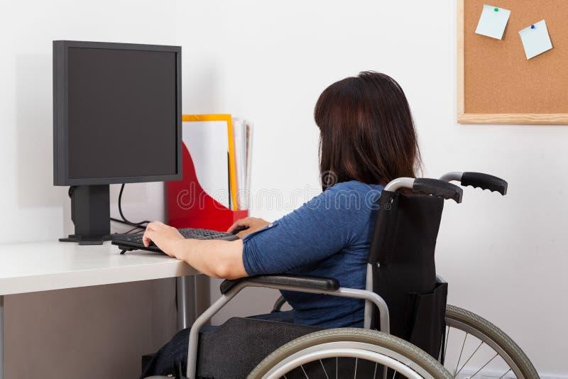 Mulher na cadeira de rodas que trabalha no escritório imagens de stock royalty free