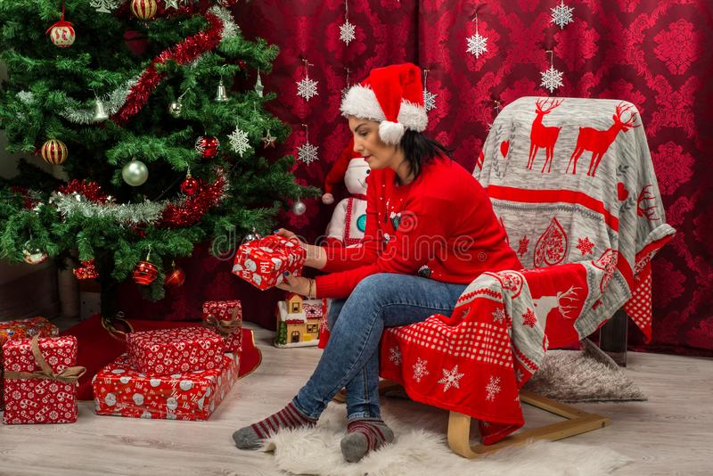 Mulher na cadeira que olha o presente do Natal fotos de stock royalty free