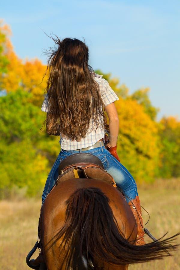 Mulher na calças de ganga que monta um cavalo foto de stock