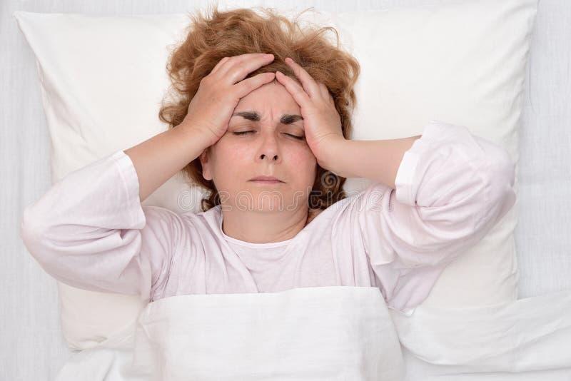 Mulher na cama com a dor de cabeça que guarda sua cabeça imagens de stock royalty free
