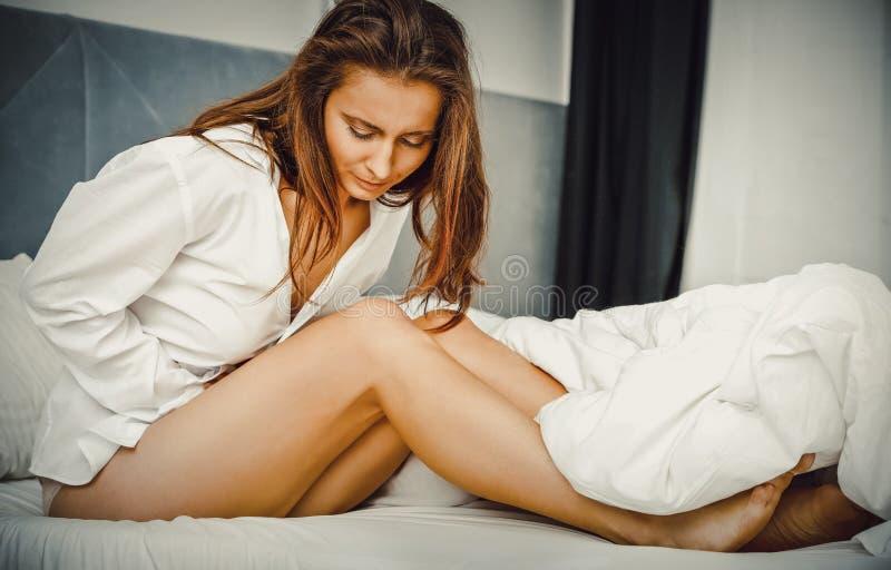Mulher na cama com dor de estômago fotografia de stock