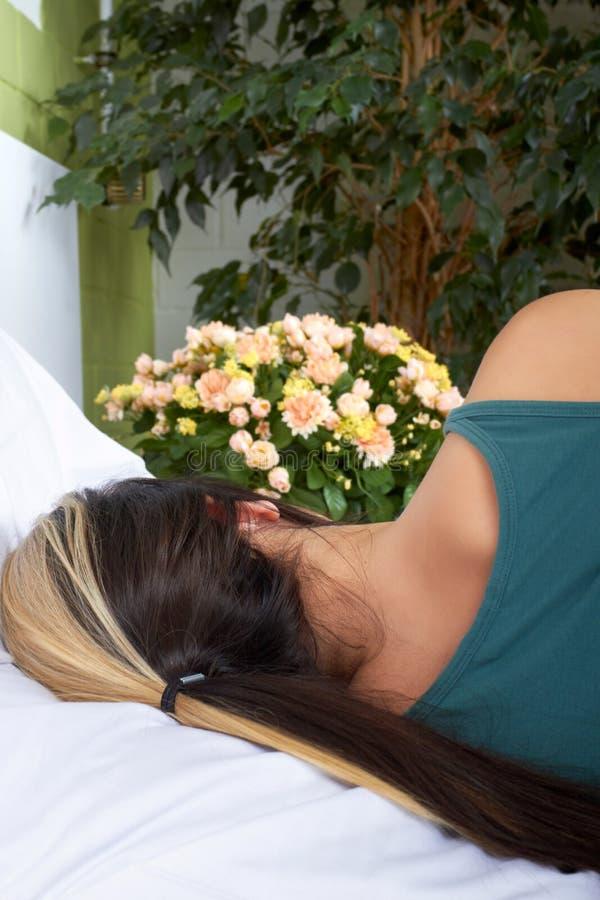 Mulher na cama com flores imagens de stock royalty free