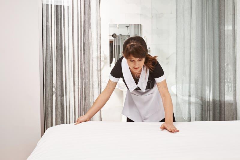 Mulher na cama de fatura uniforme da empregada doméstica Retrato do housecleaner fêmea que põe sobre coberturas novas e a sala de imagem de stock