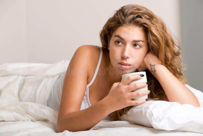 Mulher na cama que relaxa imagens de stock