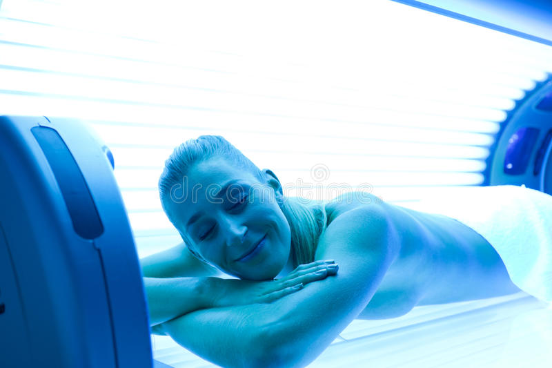 Mulher na cama tanning foto de stock royalty free