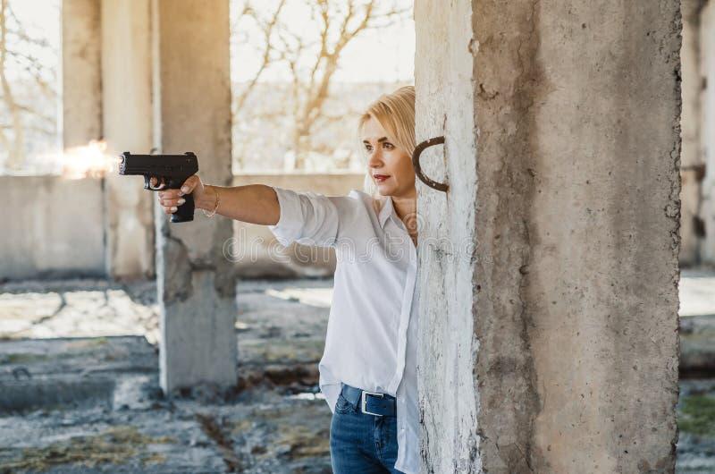 A mulher na camisa branca em uma construção abandonada dispara em uma pistola imagens de stock