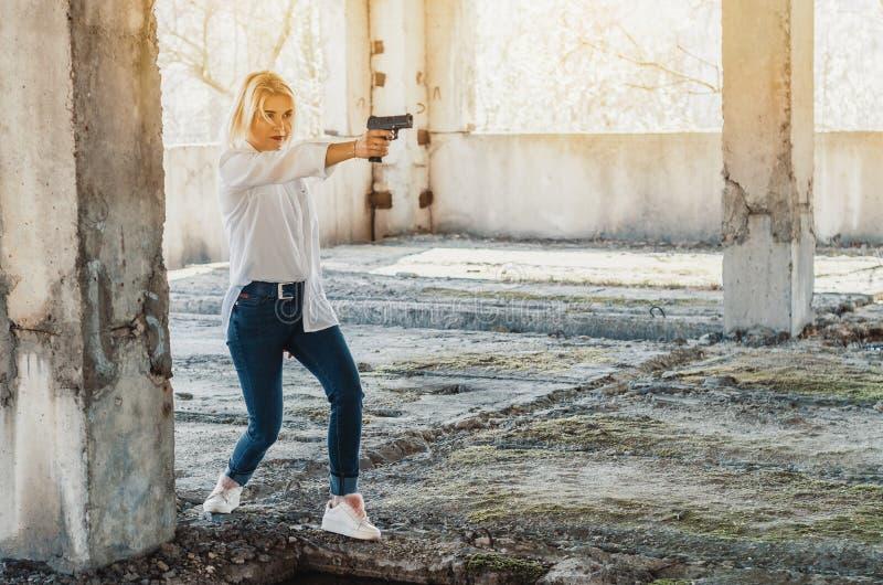 A mulher na camisa branca em uma constru??o abandonada dispara em uma pistola foto de stock royalty free