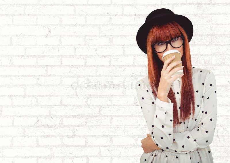 Mulher na camisa do às bolinhas com o copo de café sobre a cara contra a parede de tijolo branca foto de stock royalty free