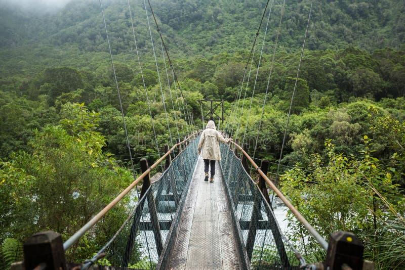 Mulher na capa de chuva que anda na ponte suspendida imagens de stock royalty free