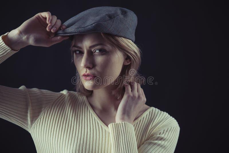 A mulher na cara misteriosa veste o kepi, fundo escuro A senhora loura olha como o detetive suspeito Conceito f?mea da l?gica foto de stock royalty free