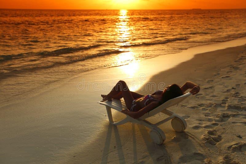 Mulher na chaise-sala de estar que relaxa na praia fotos de stock royalty free