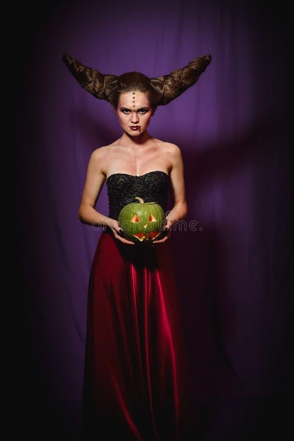 Mulher na composição de Dia das Bruxas com penteado no formulário dos chifres, rainha do diabo imagens de stock royalty free