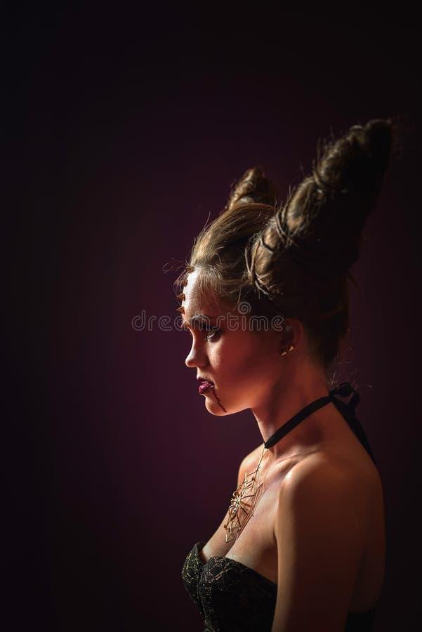 Mulher na composição de Dia das Bruxas com penteado no formulário dos chifres, rainha do diabo foto de stock royalty free
