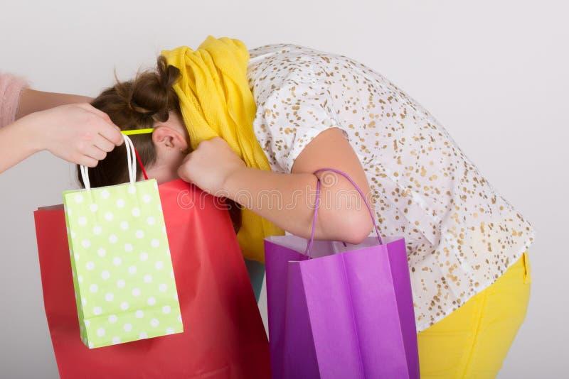 Mulher na compra com sua cabeça no saco de compras imagem de stock