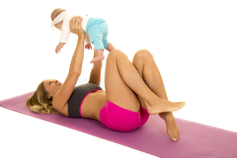 A mulher na configuração do vestuário da aptidão na esteira sustenta o bebê foto de stock