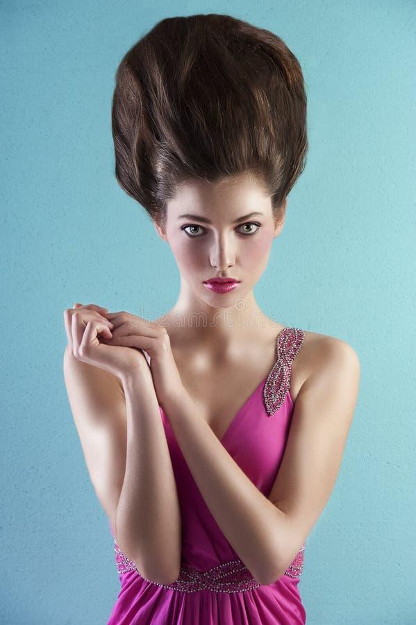 Mulher na cor-de-rosa com estilo de cabelo creativo foto de stock
