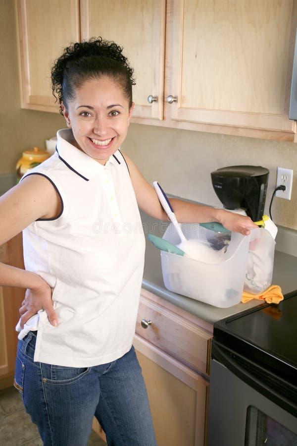 Mulher na cozinha com fontes de limpeza imagem de stock royalty free