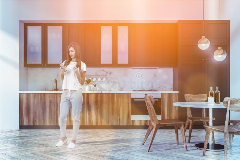 Mulher na cozinha de mármore com tabela imagens de stock