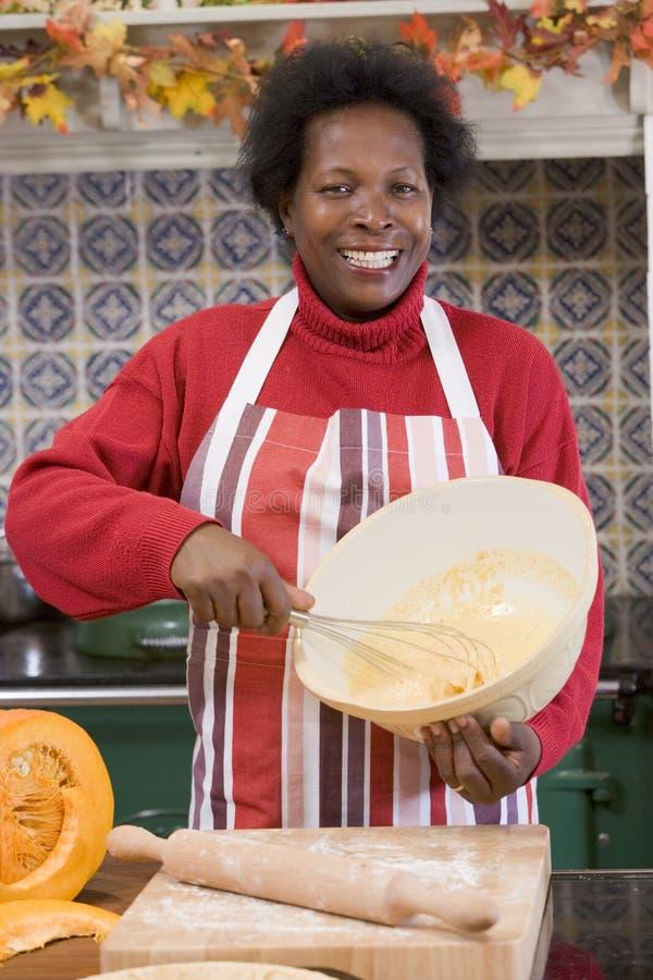 Mulher na cozinha que faz deleites de Halloween foto de stock