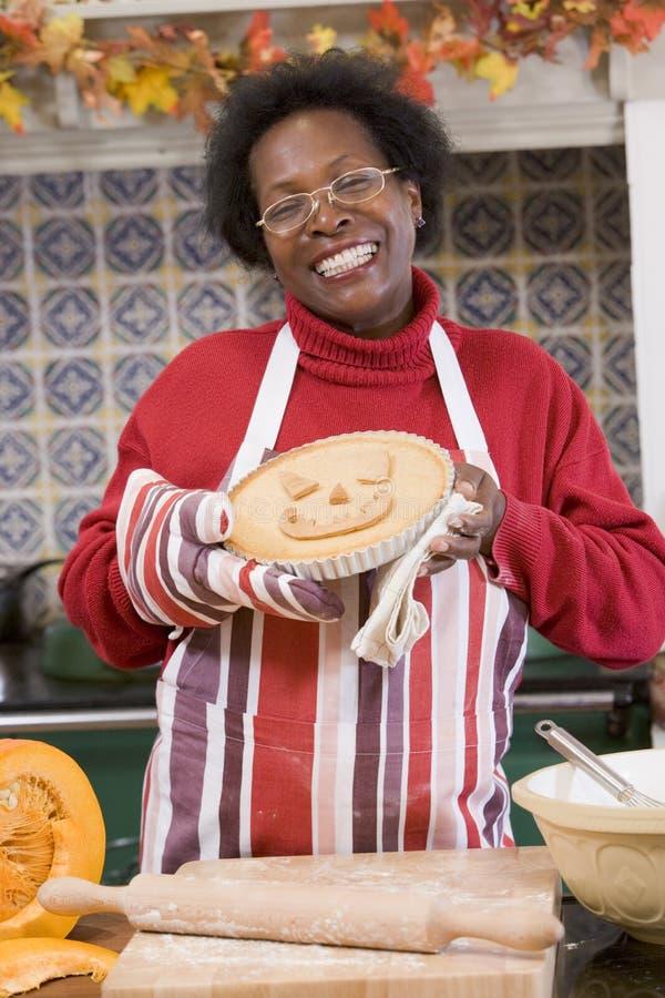 Mulher na cozinha que faz deleites de Halloween imagens de stock