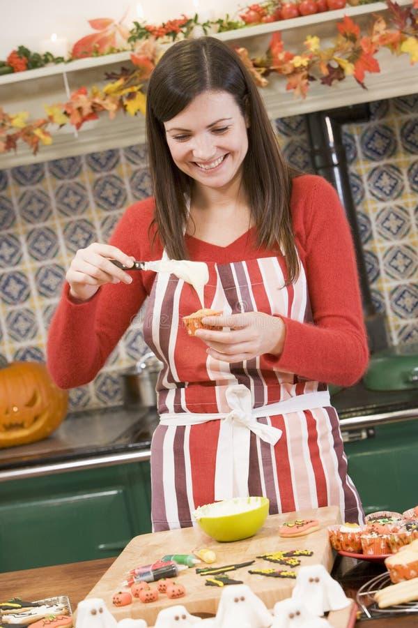 Mulher na cozinha que faz o deleite de Halloween imagens de stock