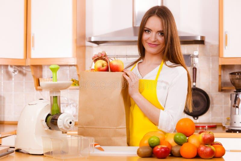 Mulher na cozinha que prepara frutos para juicing foto de stock