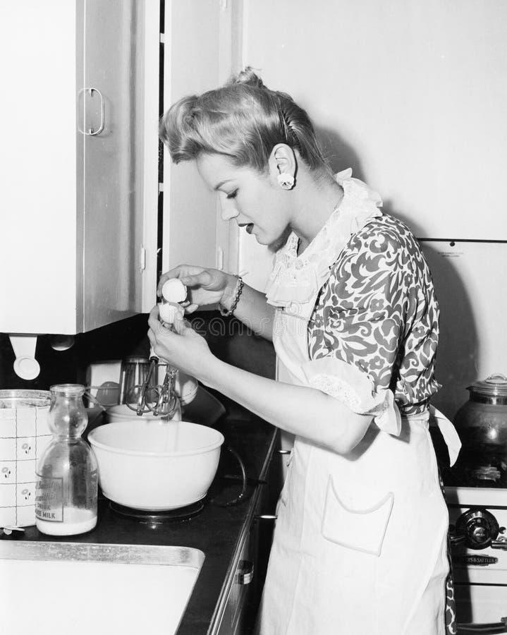 Mulher na cozinha que racha um ovo (todas as pessoas descritas não são umas vivas mais longo e nenhuma propriedade existe Garanti fotografia de stock royalty free