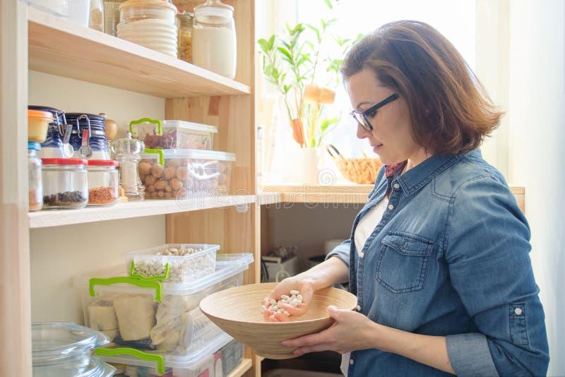 Mulher na despensa com a bacia dos feijões brancos Armário de armazenamento na cozinha fotos de stock