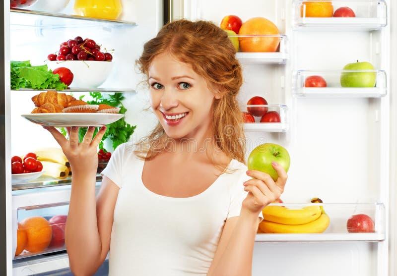 Mulher na dieta a escolher próximo entre o alimento saudável e insalubre imagem de stock royalty free