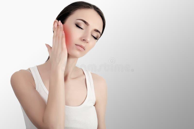 Mulher na dor Close up da jovem mulher bonita que sente a dor de dente dolorosa, cara tocante com mão Menina forçada triste que s imagens de stock royalty free