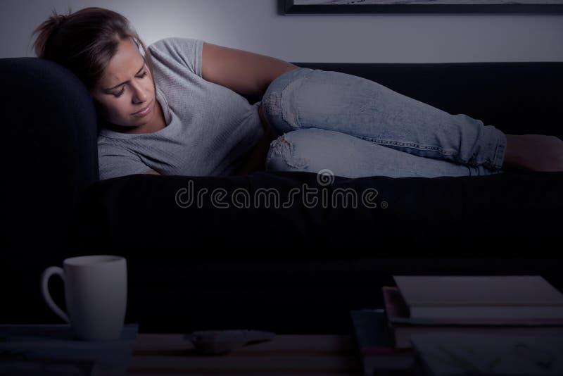 Mulher na dor em um sofá foto de stock