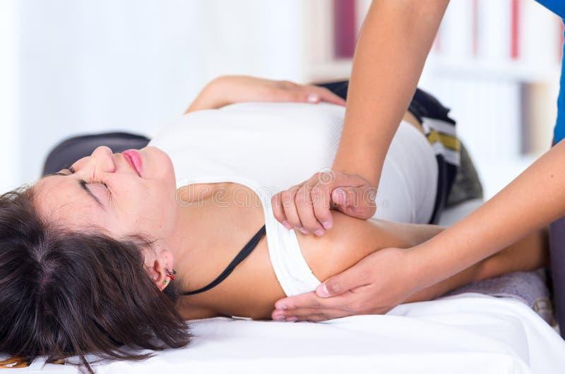 Mulher na dor que encontra-se ao obter um ombro imagens de stock royalty free