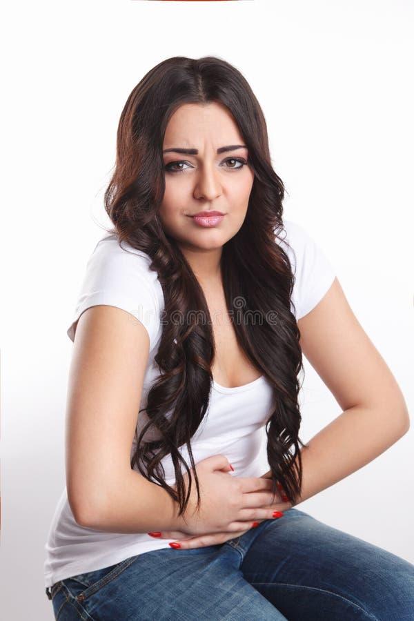 Mulher na dor que toca em seu estômago fotografia de stock royalty free