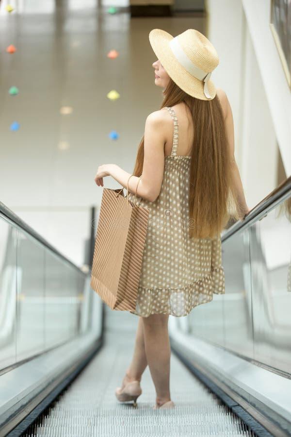 Mulher na equitação do centro de compra na escada rolante Vista traseira imagem de stock royalty free