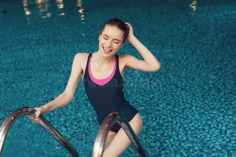 Mulher na escada da associação no gym Olha feliz, elegante e apta em uma parte fotos de stock
