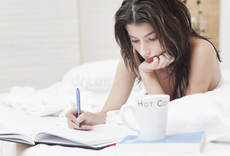 Mulher na escrita da cama em um caderno fotos de stock