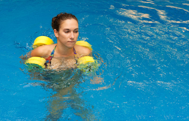 Mulher na estada da água com dumbbells imagem de stock