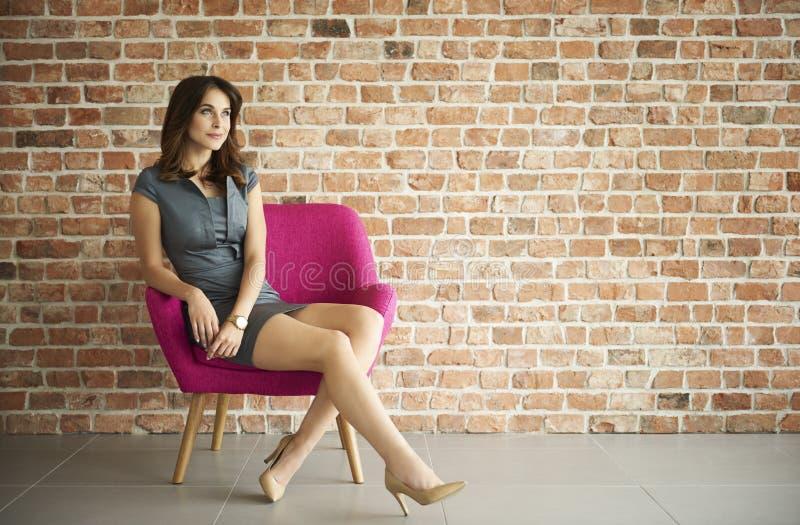 Mulher na frente da parede de tijolo fotos de stock