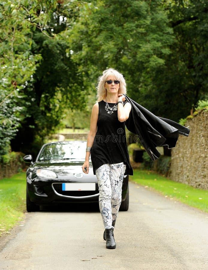 Mulher na frente de um carro de esportes fotografia de stock royalty free